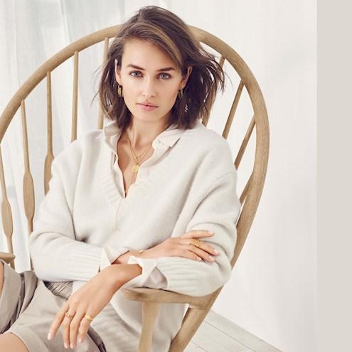 Model von Pernille Corydon sitzt in einem Schaukelstuhl, trägt einen weißen Wollpulover und darunter eine weiße Bluse und präsentiert verschiedene Schmuckstücke wie vergoldete Halsketten, Ohringe, Ringe und Armbänder.